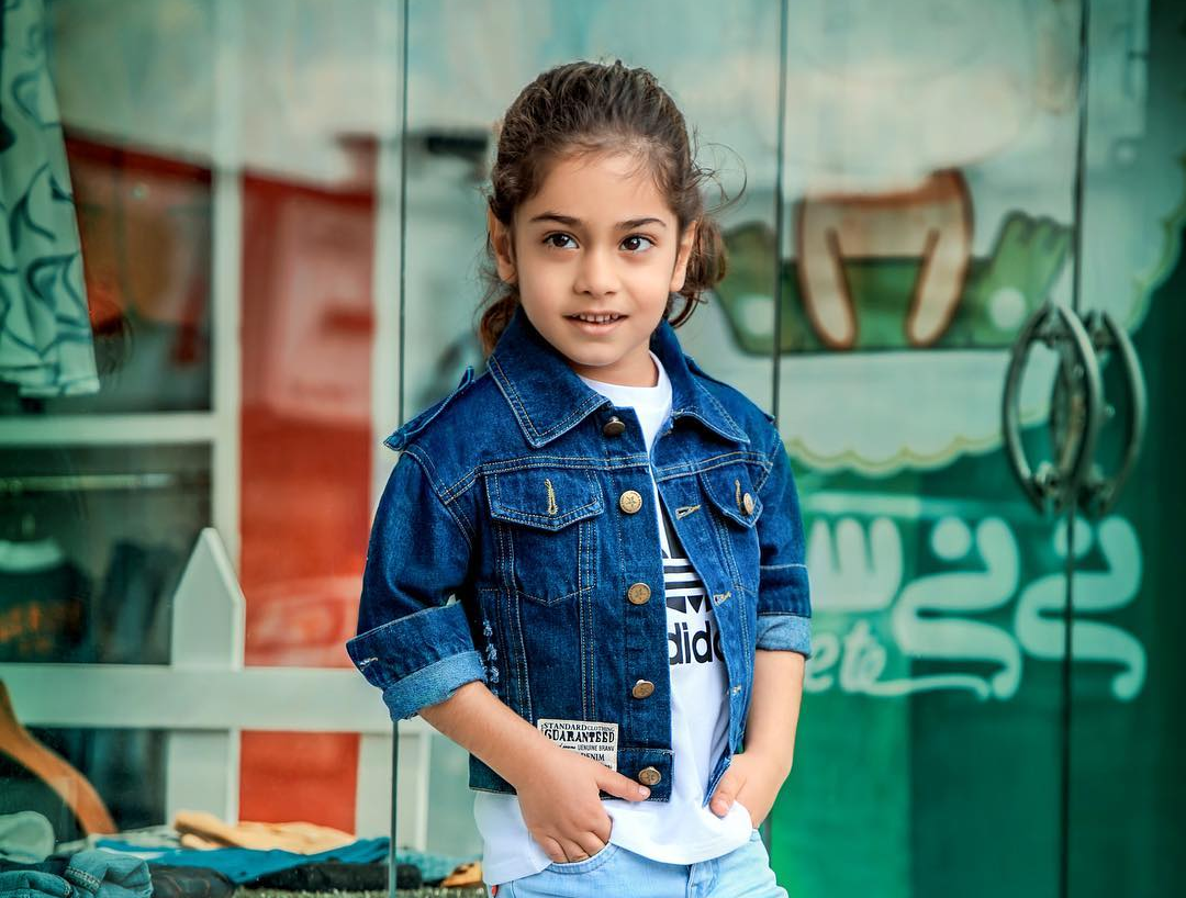 Arat in a white top and a blue jacket